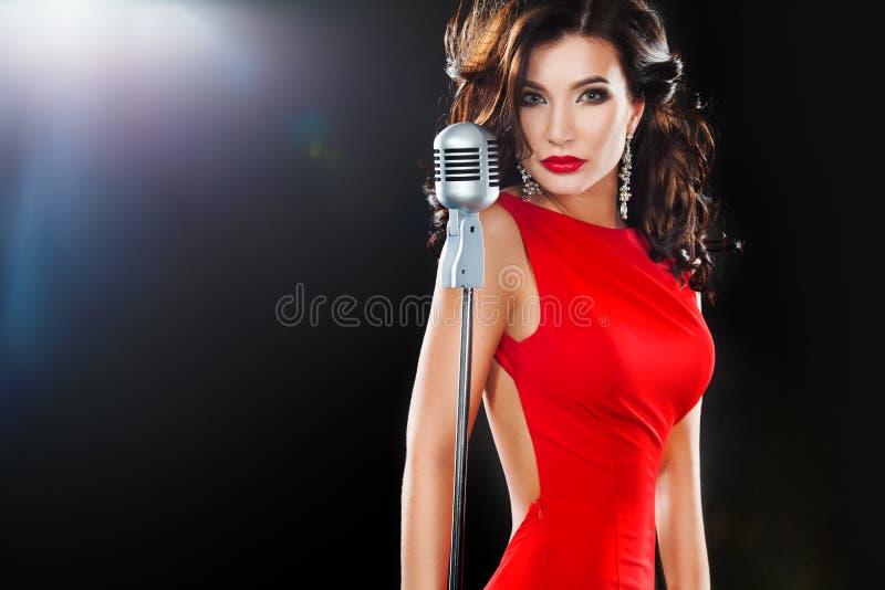 美丽的唱歌的女孩 红色礼服的秀丽妇女有话筒的 免版税库存照片