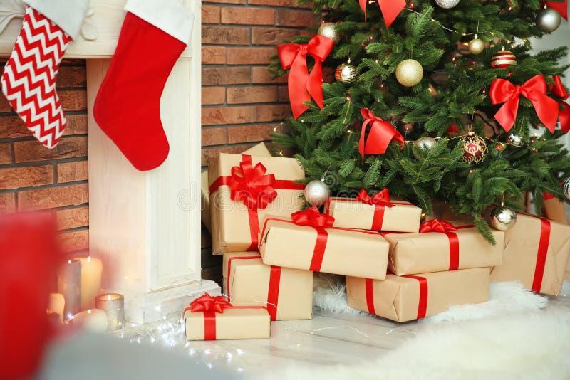 美丽的圣诞树和礼物临近装饰壁炉户内 免版税库存图片