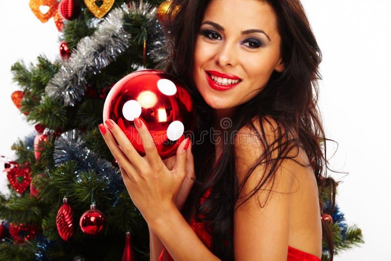美丽的圣诞老人帮手-在圣诞树旁边 库存照片