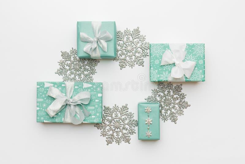 美丽的圣诞节在白色背景隔绝的礼物和银色雪花 绿松石色的被包裹的xmas箱子 免版税图库摄影