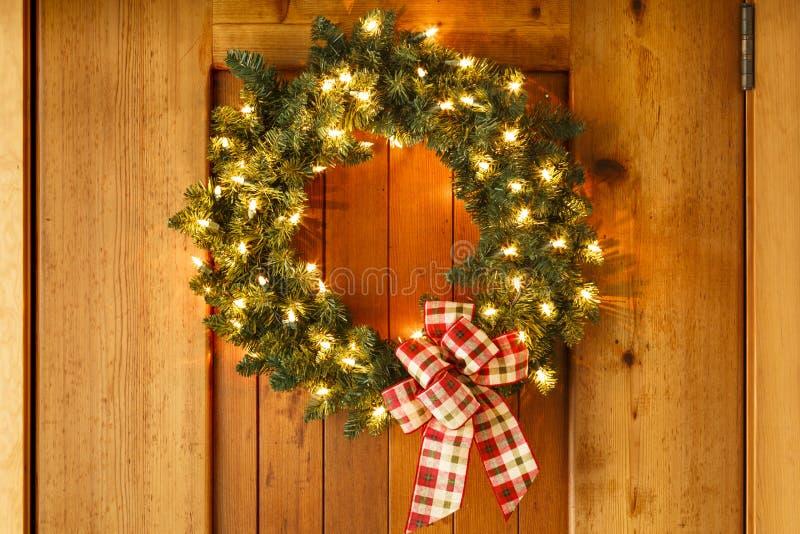 美丽的圣诞节花圈家装饰在房子的前门点燃 库存图片