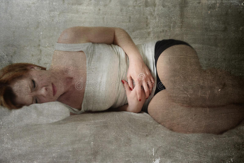 年轻美丽的在举行难看的东西的腹部的妇女遭受的胃痉挛编辑 免版税库存照片