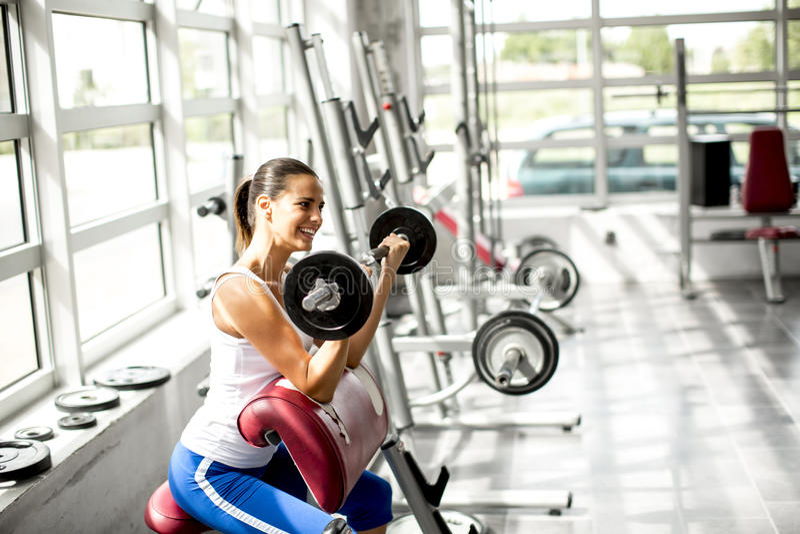 年轻美丽的在健身房的妇女举的重量 图库摄影