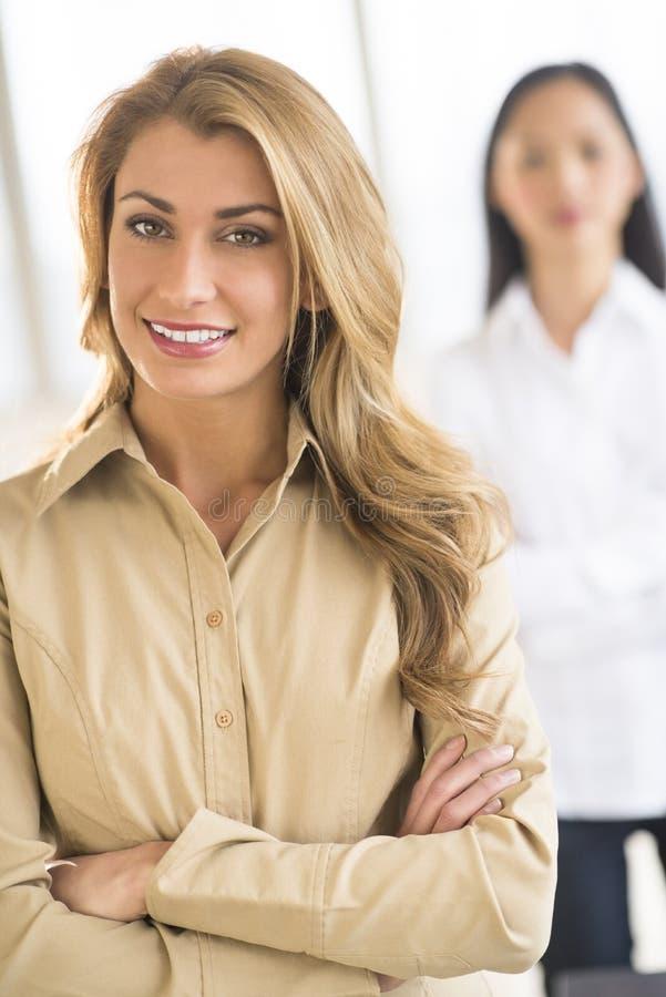 美丽的在办公室横渡的女实业家常设胳膊 免版税库存照片