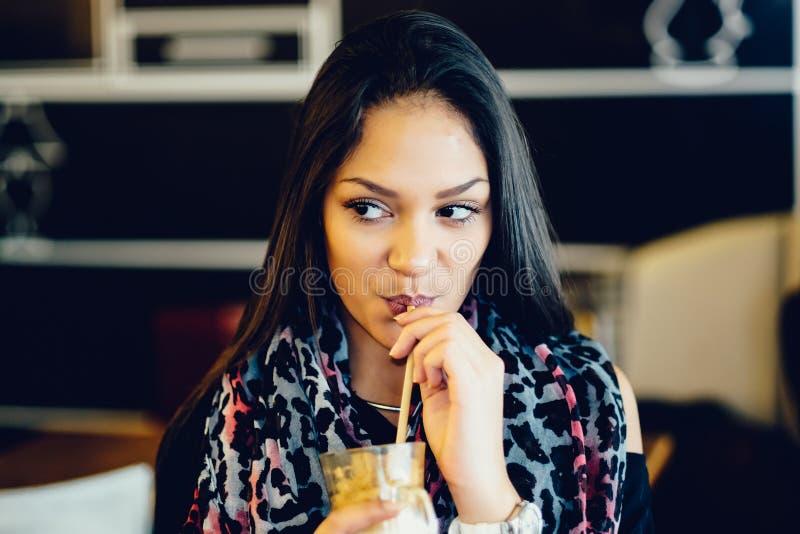 美丽的在咖啡馆的女孩饮用的冰上等咖啡震动 免版税图库摄影