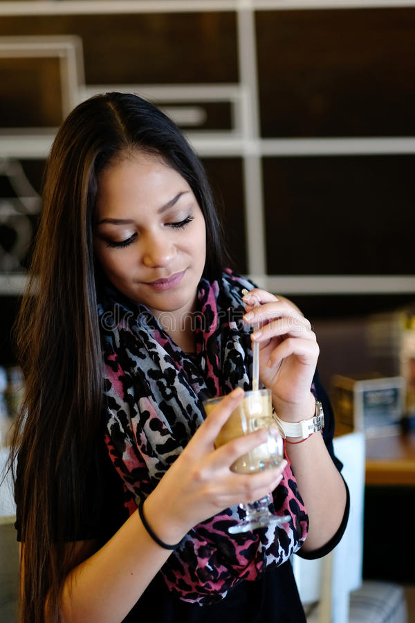 美丽的在咖啡馆的女孩饮用的冰上等咖啡震动 库存图片