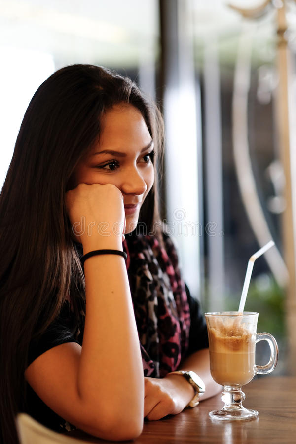 美丽的在咖啡馆的女孩饮用的冰上等咖啡震动 免版税库存图片