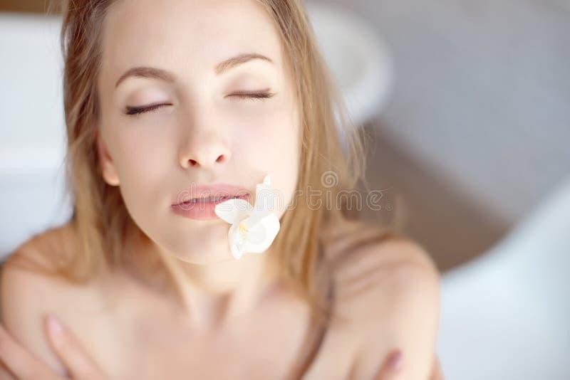 美丽的在嘴的少妇和花的特写镜头面孔有健康皮肤的 库存图片