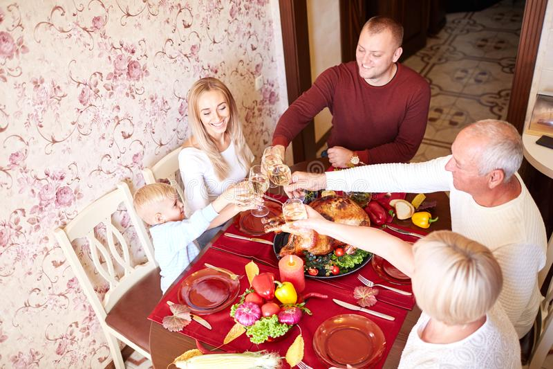 美丽的在感恩的家庭欢呼的玻璃在被弄脏的背景 愉快的庆祝的概念 免版税库存图片