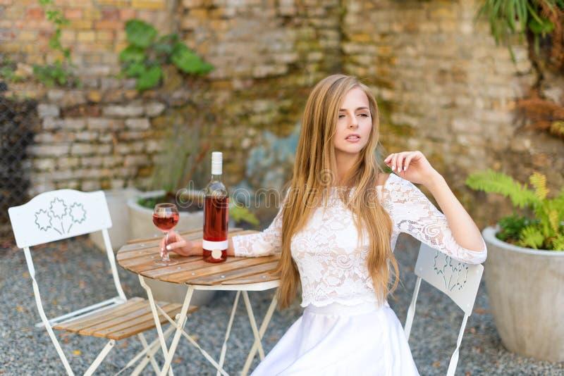 美丽的在户外咖啡馆的妇女饮用的酒 年轻白肤金发的秀丽画象在获得的葡萄园里乐趣,享用a 免版税库存图片
