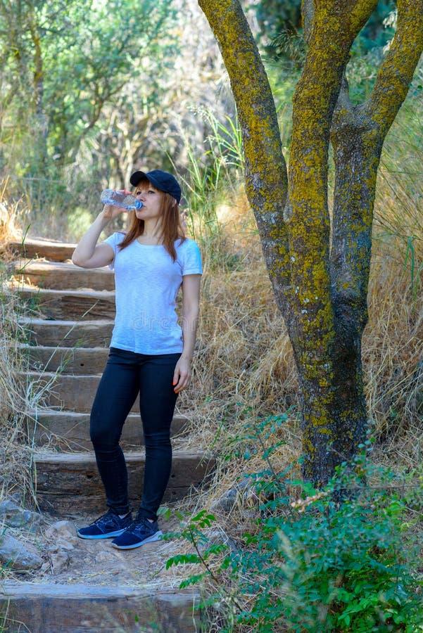 美丽的在旅行或旅行以后的成功运动员妇女饮用水在晴朗的夏日在森林里 免版税库存图片