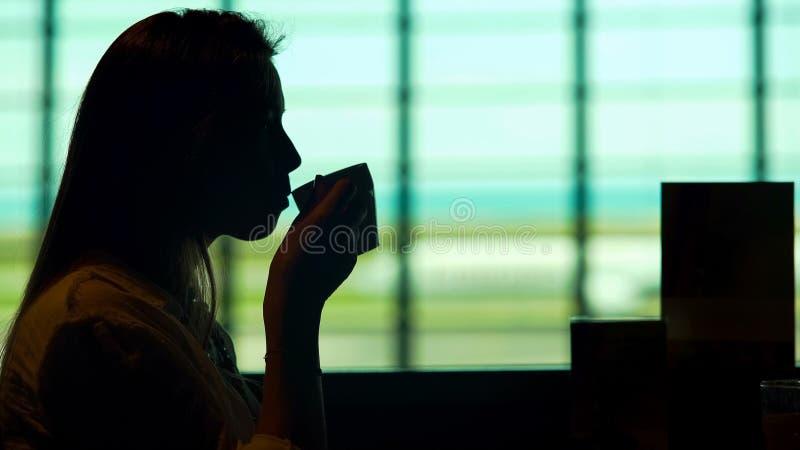 美丽的在机场餐馆和饮用的咖啡的妇女等待的飞机 库存图片