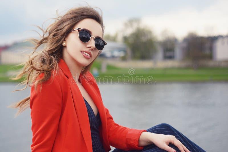 美丽的在河沿的女孩佩带的太阳镜 女孩坐码头和lookingat河 户外美丽的女孩 免版税图库摄影