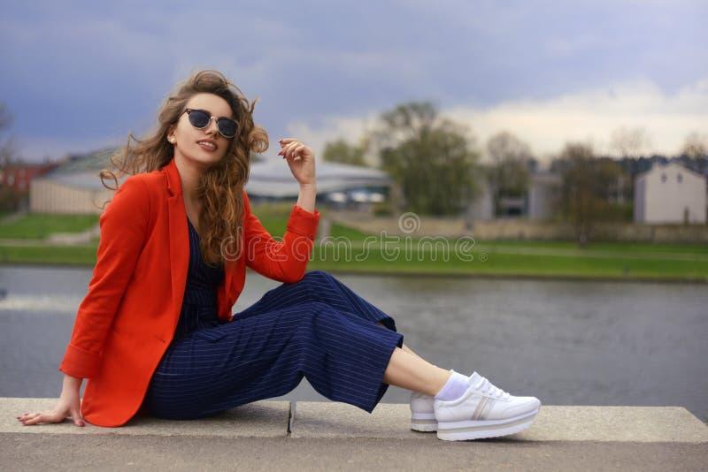 美丽的在河沿的女孩佩带的太阳镜 女孩坐码头和lookingat河 户外美丽的女孩 库存照片