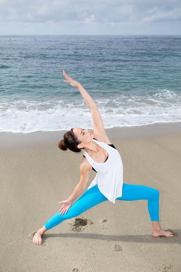 美丽的在海滩的女子实践的瑜伽 库存照片