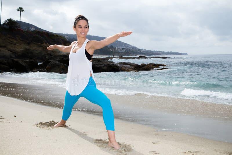美丽的在海滩的女子实践的瑜伽 图库摄影