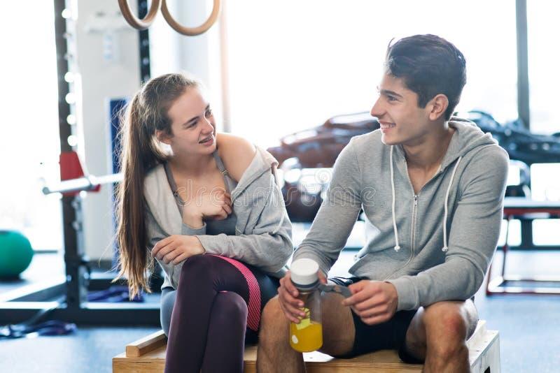 美丽的在现代crossfit健身房谈话的年轻人适合的夫妇 图库摄影