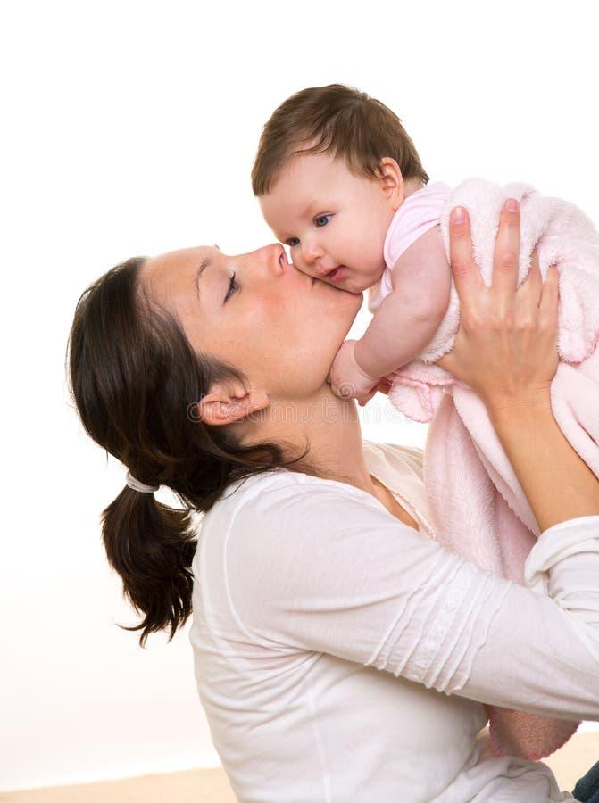 美丽的在白色的母亲亲吻的女婴拥抱 库存图片