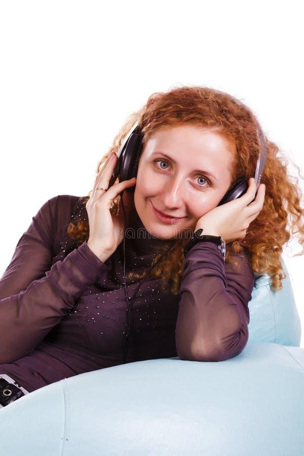 美丽的在耳机的妇女listning的音乐 库存图片