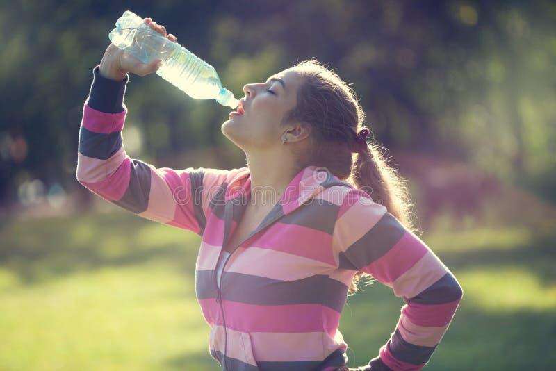 年轻美丽的在行使的妇女饮用水在同水准以后 免版税图库摄影