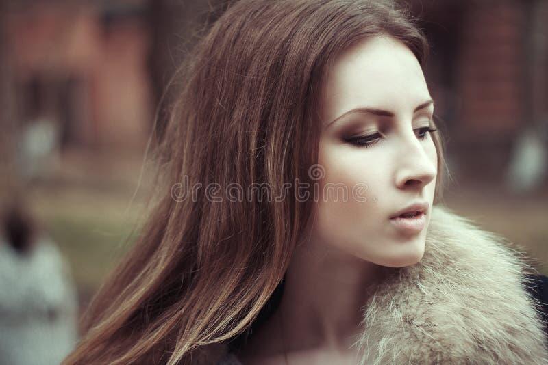 美丽的在街道上的少妇画象佩带的皮大衣 免版税库存照片