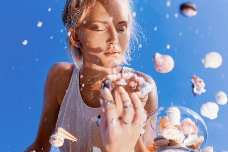 美丽的在镜子画象的年轻女人式样反射与海壳 库存图片