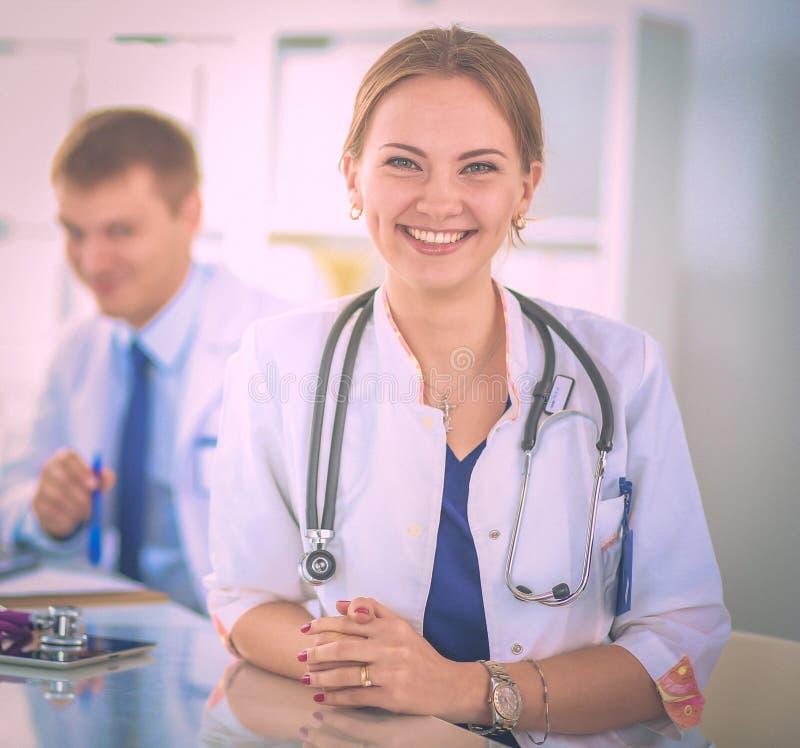 美丽的坐在书桌的年轻人微笑的女性医生 免版税库存照片