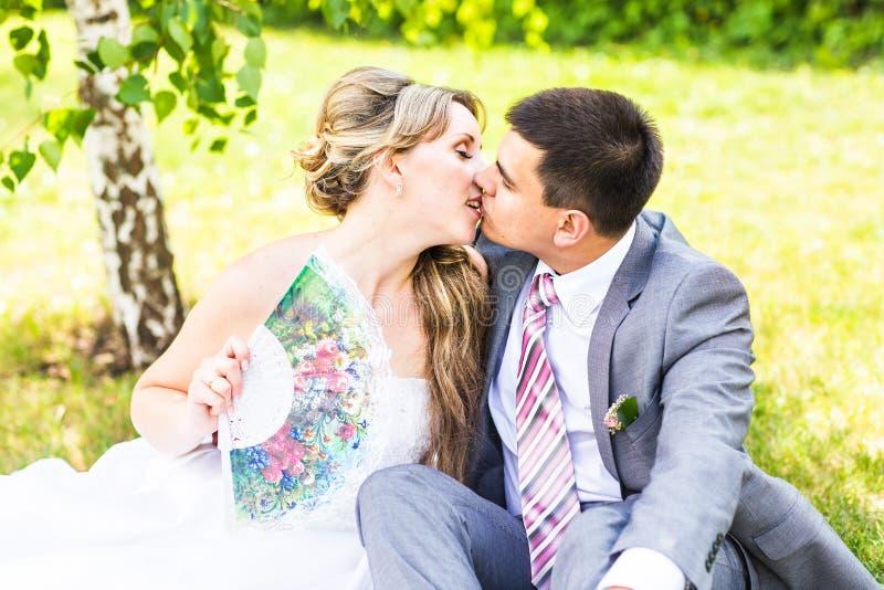 美丽的坐在草和亲吻的新娘和新郎 夫妇婚礼年轻人 库存照片