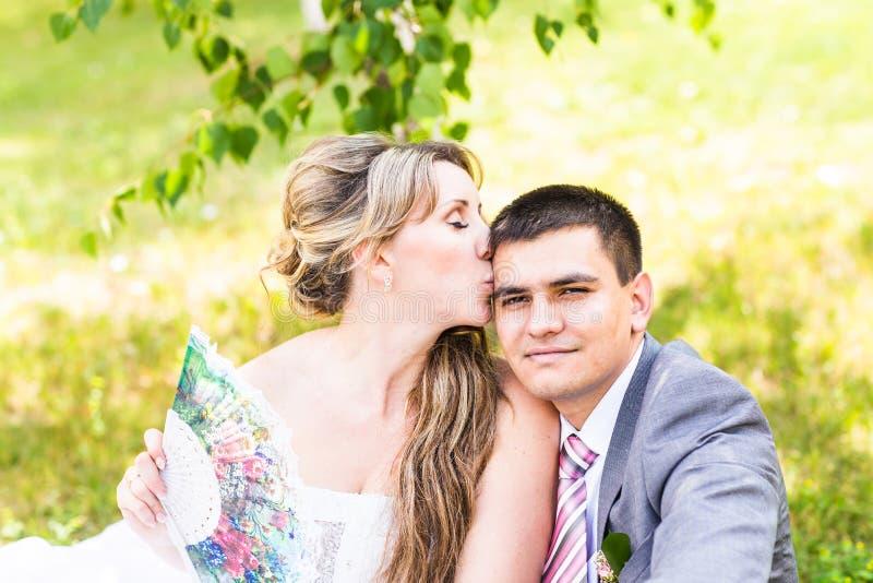 美丽的坐在草和亲吻的新娘和新郎 夫妇婚礼年轻人 免版税库存图片