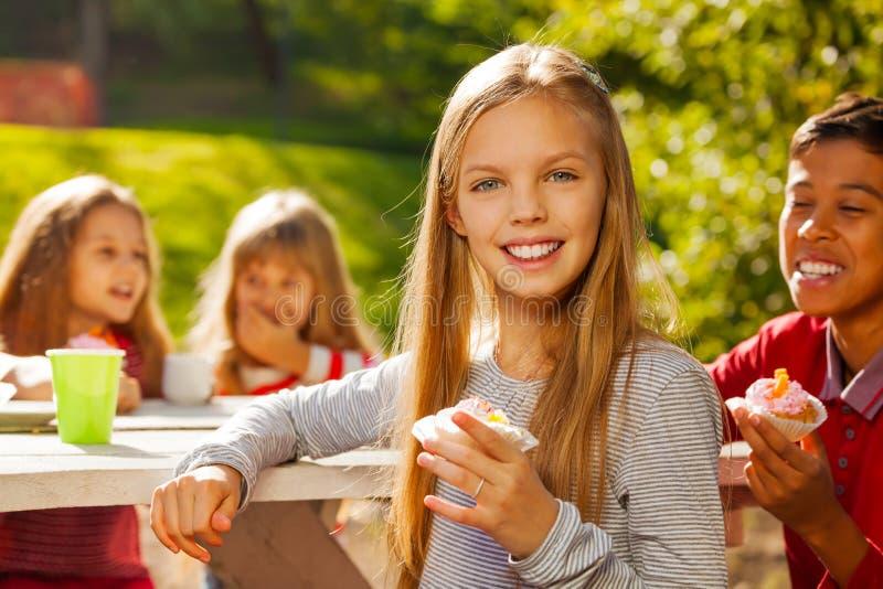 美丽的坐女孩和愉快的孩子外面 免版税库存照片
