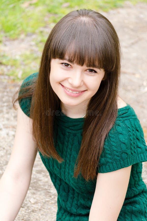 年轻美丽的坐户外愉快的微笑的&看的照相机的妇女深色的女孩特写镜头画象  库存照片