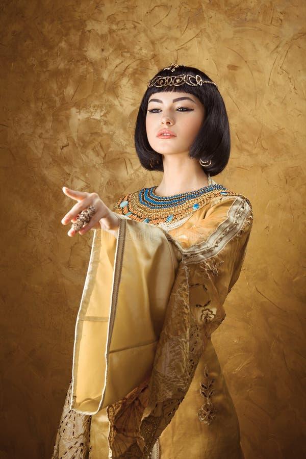 美丽的埃及妇女喜欢指向手指在金黄背景的帕特拉 免版税图库摄影