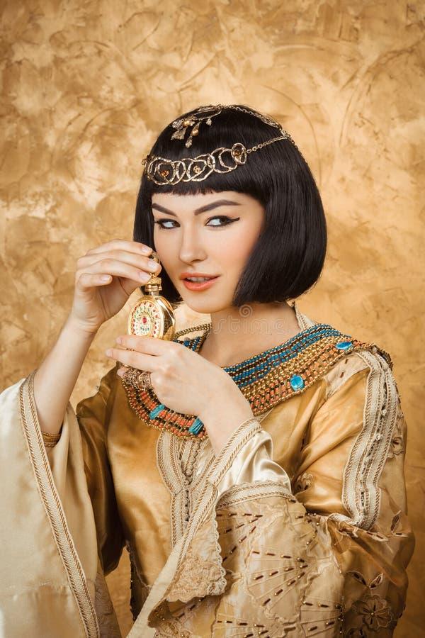 美丽的埃及妇女喜欢有香水瓶的帕特拉在金黄背景 库存图片