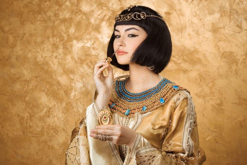 美丽的埃及妇女喜欢有香水瓶的帕特拉在金黄背景 免版税库存照片