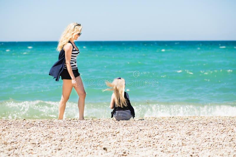 美丽的基于海滩的妇女和她迷人的女儿 库存照片