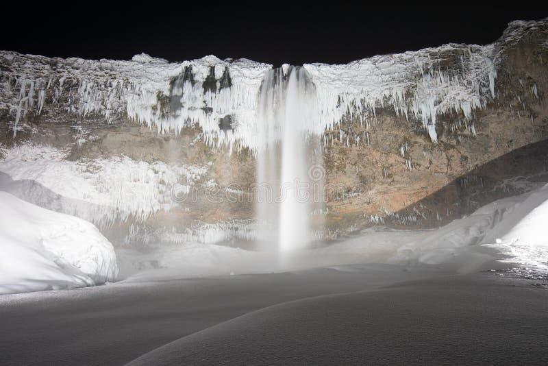 美丽的塞里雅兰瀑布在寒冷冬天夜,在星下的冰岛,欧洲瀑布 免版税库存图片