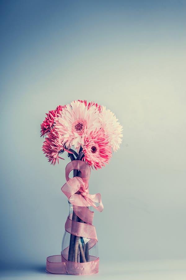 美丽的大丁草开花在glas花瓶的束有桃红色丝带的 库存照片