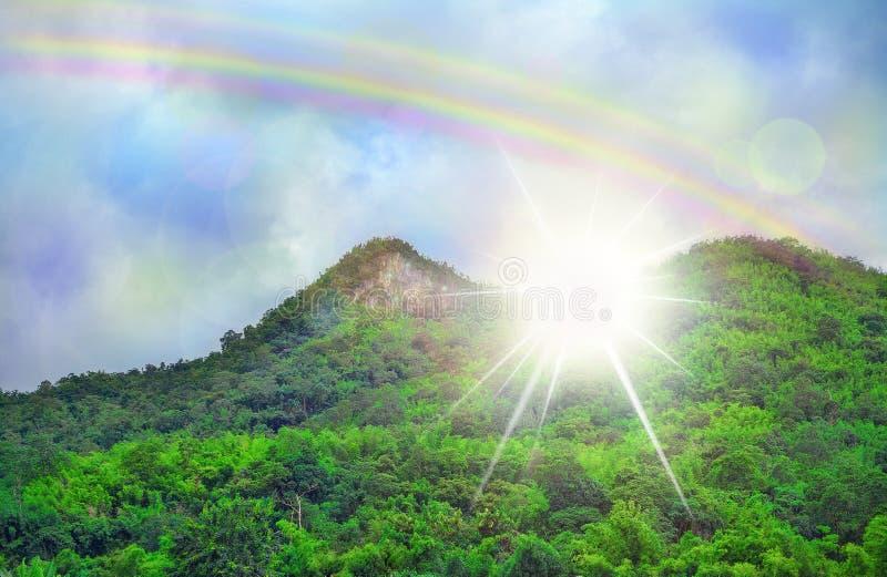 美丽的天空云彩彩虹,绿色山剧烈的光 免版税库存照片