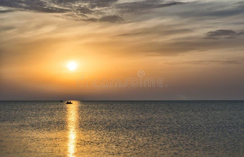 美丽的太阳在水,小船的人民反射了在 免版税库存图片