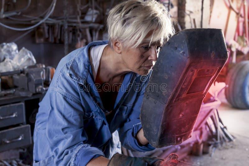 美丽的夫人在工作在他的老车间 库存照片