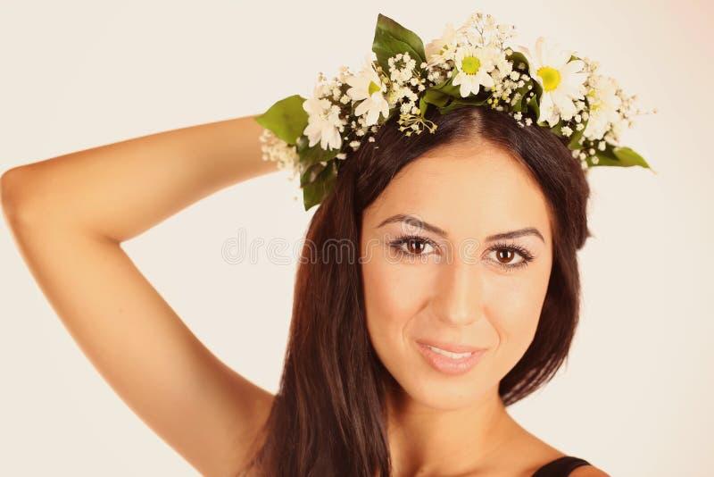 美丽的夫人在有花的演播室在她的头发 免版税库存图片