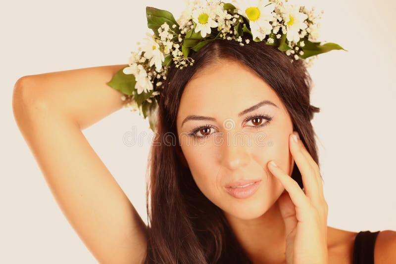 美丽的夫人在有花的演播室在她的头发 库存照片