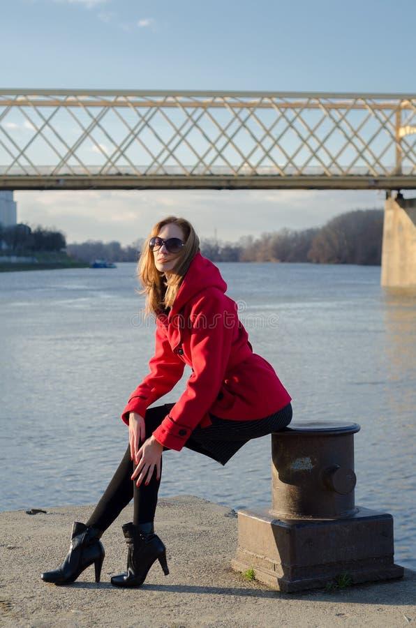 美丽的夫人坐河船坞 免版税图库摄影