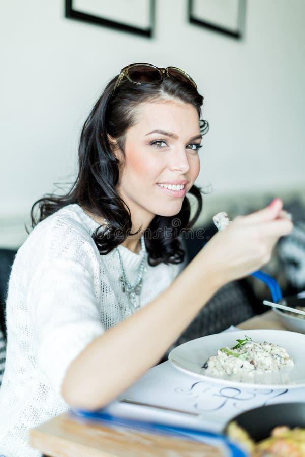 美丽的夫人有膳食在餐馆 免版税库存图片