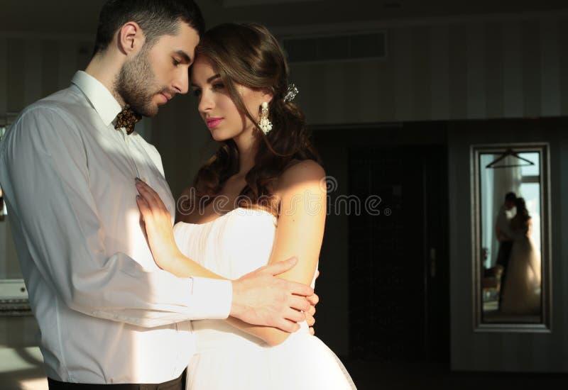 美丽的夫妇、新郎和新娘穿婚礼衣裳,拥抱在卧室 免版税库存图片