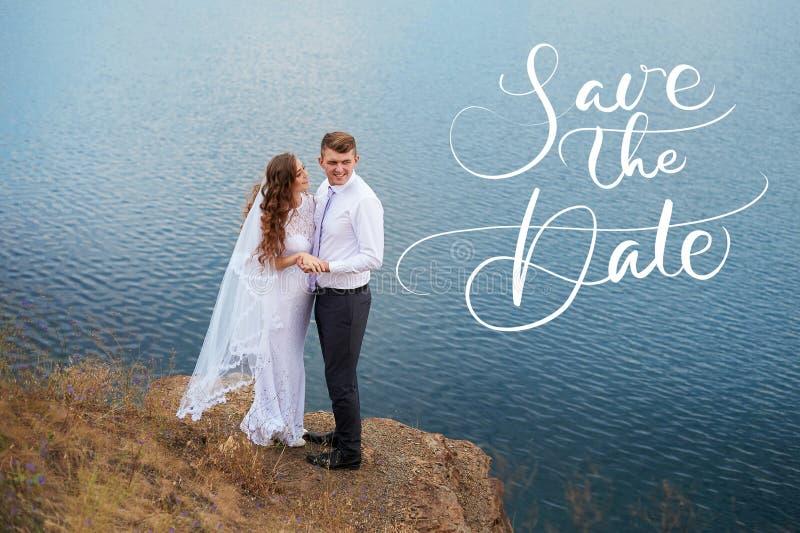 年轻美丽的夫妇新娘和新郎在婚礼由湖走,并且词保存日期 书法字法 免版税图库摄影