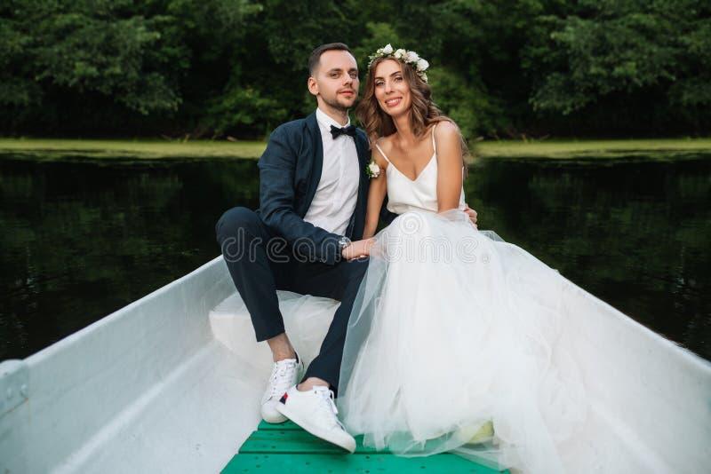 美丽的夫妇新郎和新娘在河船附近 以美好的自然和日落为背景 图库摄影