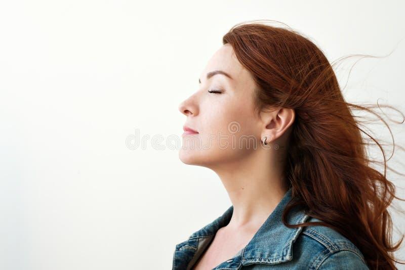 美丽的头发的纵向红色妇女 她在一个被启发的方式看,作梦关于某事 免版税库存图片