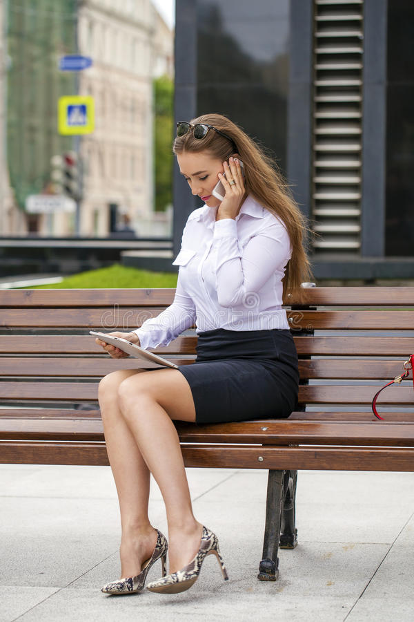 年轻美丽的女商人坐在晴朗的c的一条长凳 免版税库存照片