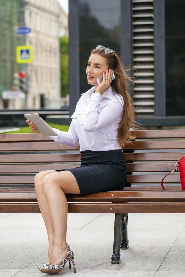 年轻美丽的女商人坐在晴朗的c的一条长凳 库存照片